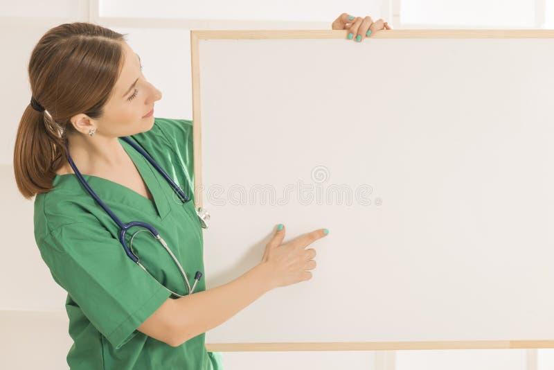 Gelukkige glimlachende jonge mooie vrouwelijke arts die leeg gebied voor teken tonen of copyspace royalty-vrije stock foto