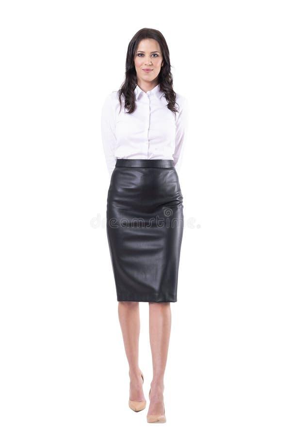 Gelukkige glimlachende jonge volwassen bedrijfsvrouw of leraar die naar camera met handen achter rug lopen stock foto