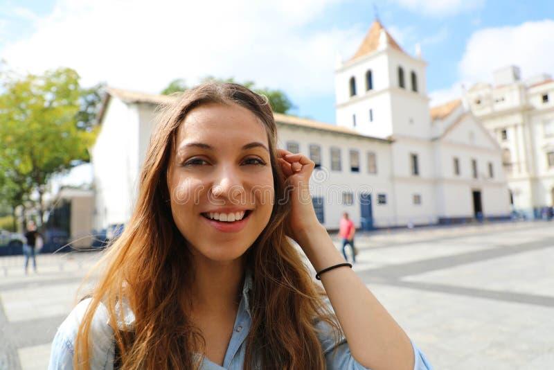 Gelukkige glimlachende jonge vrouw in de stadscentrum van Sao Paulo met Patio do Colegio ori?ntatiepunt op de achtergrond, Sao Pa royalty-vrije stock fotografie