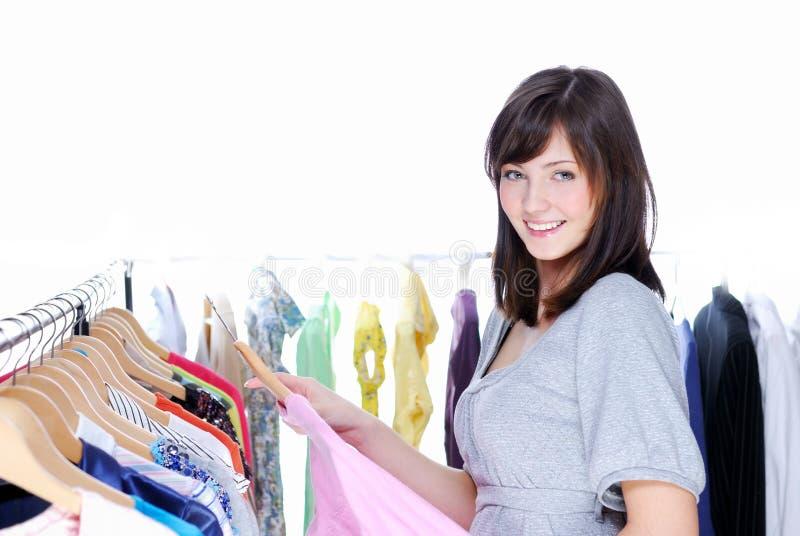 Gelukkige glimlachende jonge vrouw die kleding kiest stock foto's
