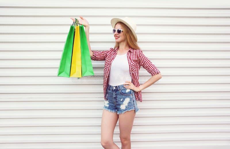 Gelukkige glimlachende jonge vrouw met kleurrijke het winkelen zakken in de zomer om strohoed, geruit overhemd, borrels op witte  royalty-vrije stock foto's