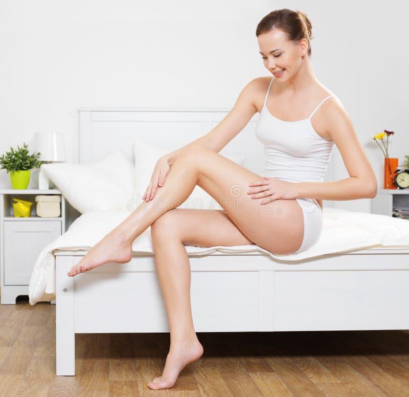 Gelukkige glimlachende jonge vrouw met mooie benen stock fotografie