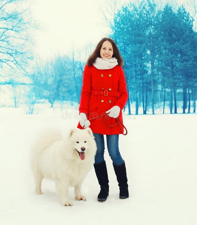 Gelukkige glimlachende jonge vrouweneigenaar die met witte Samoyed-hond in de winter lopen royalty-vrije stock foto