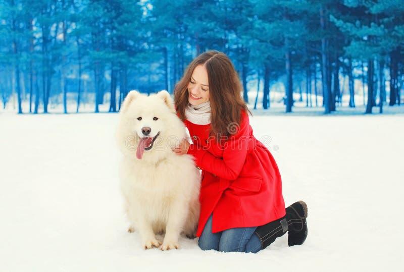 Gelukkige glimlachende jonge vrouweneigenaar met witte Samoyed-hond op sneeuw in de winter stock fotografie