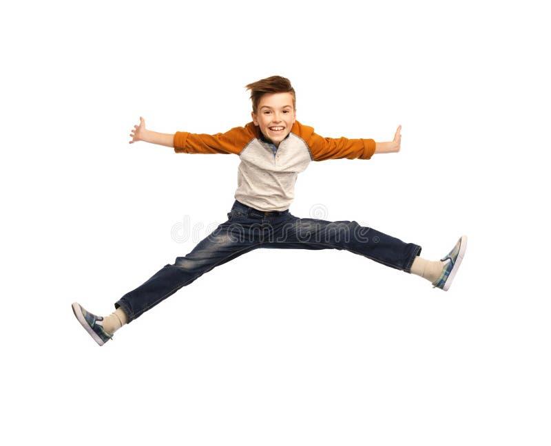 Gelukkige glimlachende jongen die in lucht springen stock foto's