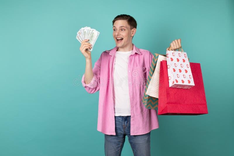 Gelukkige glimlachende jongen in roze overhemd met geld en het winkelen ruggen in handen royalty-vrije stock foto's