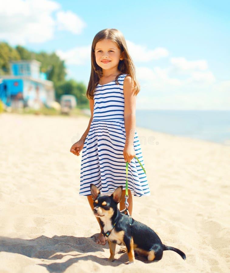 Gelukkige glimlachende kindmeisje en hond die op strand in de zomer lopen stock foto