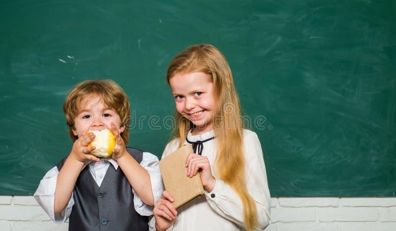 Gelukkige glimlachende leerlingen die bij het bureau trekken Basisschooljonge geitjes in klaslokaal op school Leraarsschoolmeisje stock afbeelding