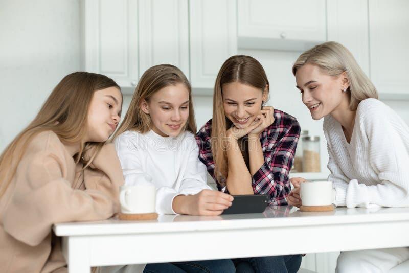 Gelukkige glimlachende lesbische familie in vrijetijdskleding, twee dochters en de zitting van hun mamma samen bij de lijst in royalty-vrije stock foto