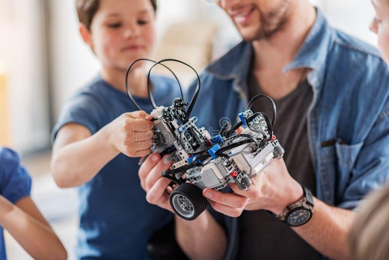 Gelukkige glimlachende mens die technisch stuk speelgoed houden stock afbeeldingen