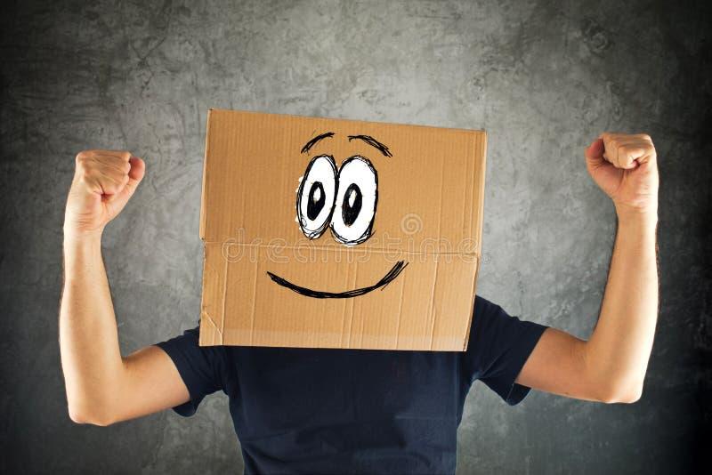 Gelukkige glimlachende mens met kartondoos op zijn hoofd en opgeheven vuist royalty-vrije stock foto's