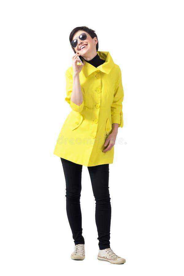 Gelukkige glimlachende modieuze vrouw die op de mobiele telefoon spreken die omhoog eruit zien stock fotografie