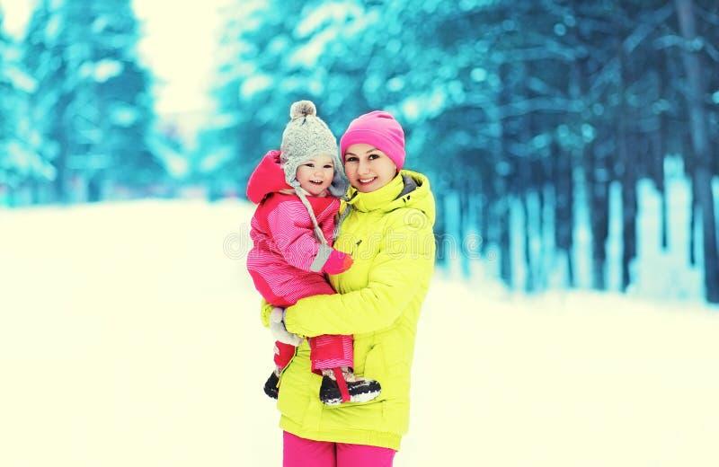 Gelukkige glimlachende moeder en baby die in de sneeuwwinter lopen royalty-vrije stock afbeelding
