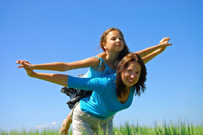 Gelukkige glimlachende Moeder en de dochtervlieg in hemel stock afbeeldingen