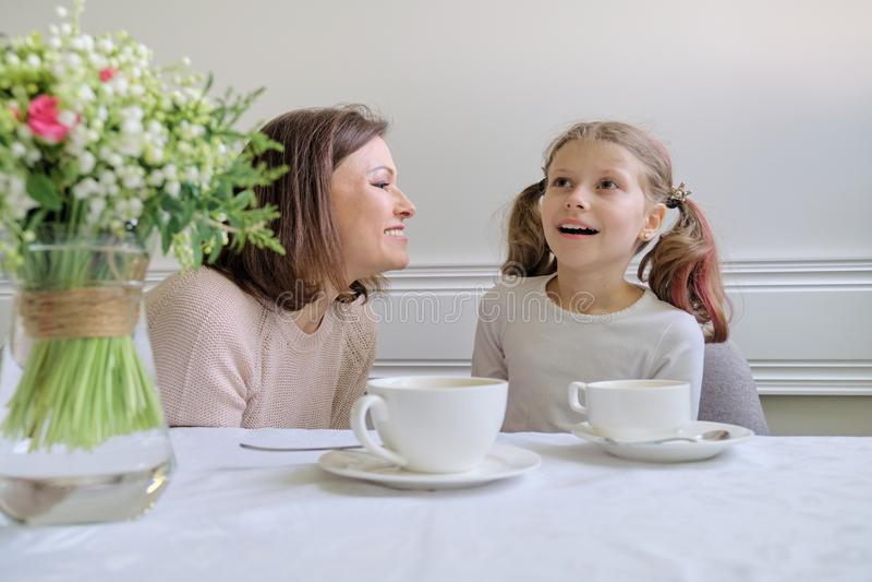 Gelukkige glimlachende moeder en weinig dochter die bij lijst van koppen drinken royalty-vrije stock foto's