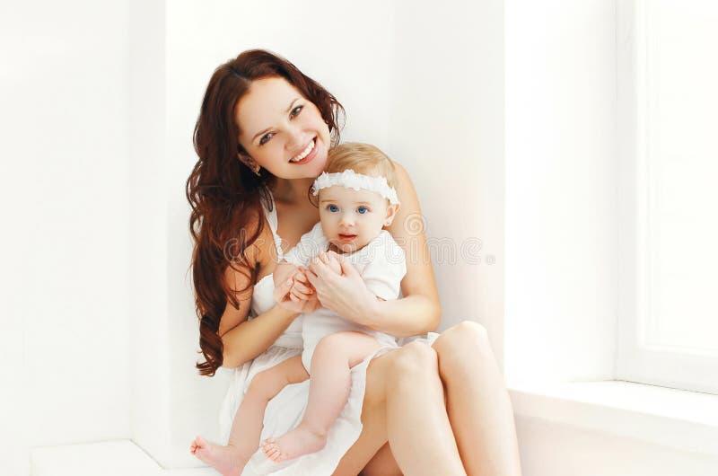 Gelukkige glimlachende moeder met baby thuis in witte ruimte royalty-vrije stock fotografie