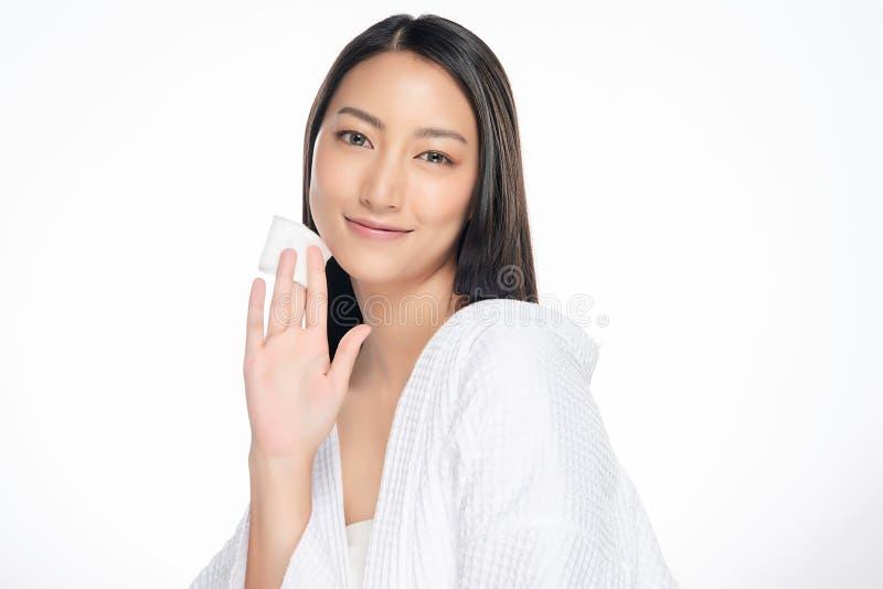 Gelukkige glimlachende mooie Aziatische vrouw die katoenen stootkussen schoonmakende huid gebruiken stock foto's