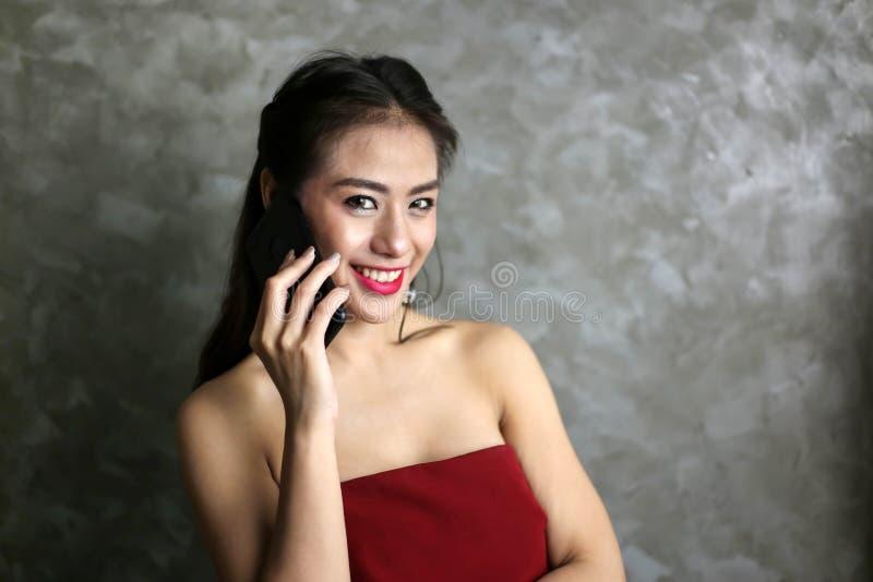 Gelukkige glimlachende mooie jonge sexy vrouw in het rode gebruik van de partijkleding stock foto's