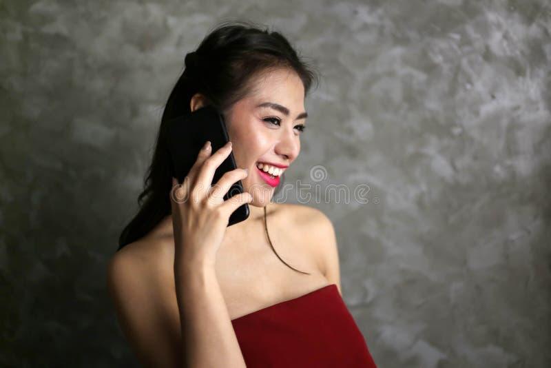 Gelukkige glimlachende mooie jonge sexy vrouw in het rode gebruik van de partijkleding royalty-vrije stock afbeelding
