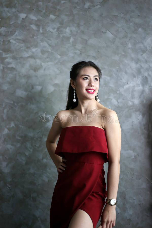 Gelukkige glimlachende mooie jonge sexy vrouw in rode partijkleding stock foto