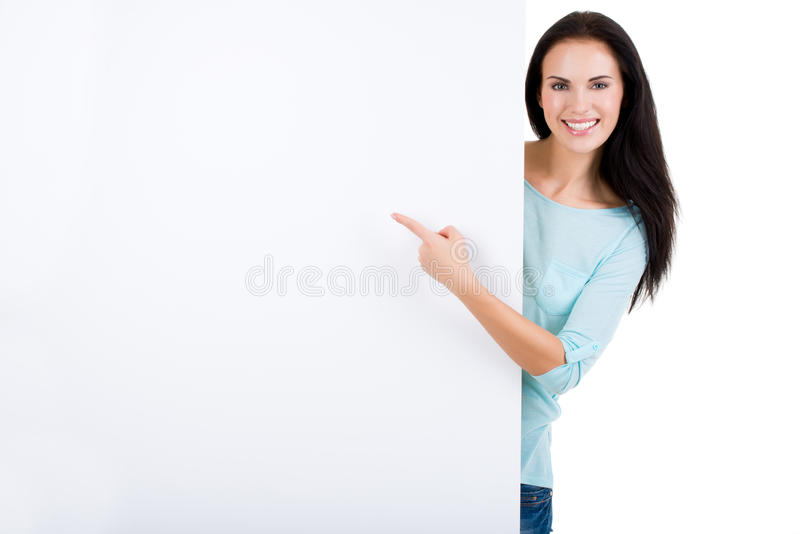 Gelukkige glimlachende mooie jonge vrouw die leeg uithangbord tonen stock afbeeldingen