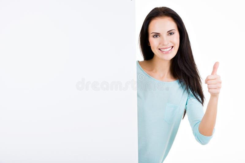 Gelukkige glimlachende mooie jonge vrouw die leeg uithangbord tonen royalty-vrije stock afbeelding