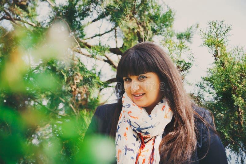 Gelukkige glimlachende mooie te zware jonge vrouw in donkerblauw jasje en sjaal met anker in openlucht Zeker plus groottevrouw stock fotografie