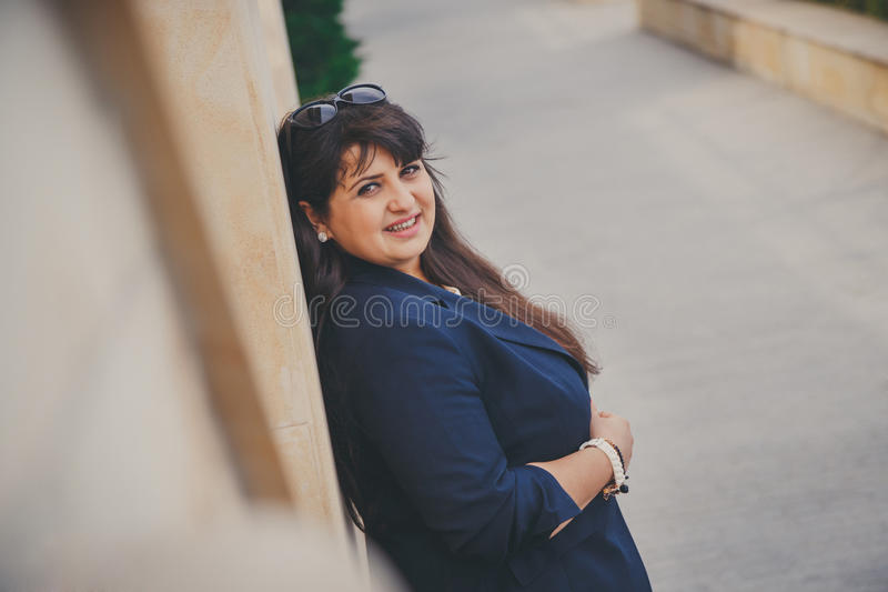 Gelukkige glimlachende mooie te zware jonge vrouw in donkerblauw jasje in openlucht bij de straat Zekere vette jonge vrouw Xxlvro royalty-vrije stock fotografie