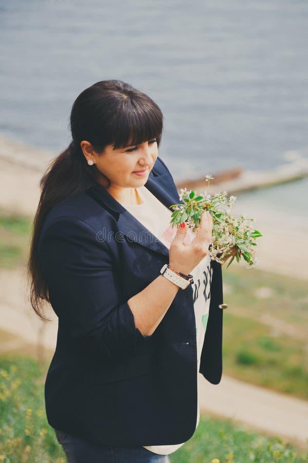 Gelukkige glimlachende mooie te zware jonge vrouw in donkerblauw jasje in openlucht dichtbij aan overzees met bloemen Zekere vett royalty-vrije stock fotografie