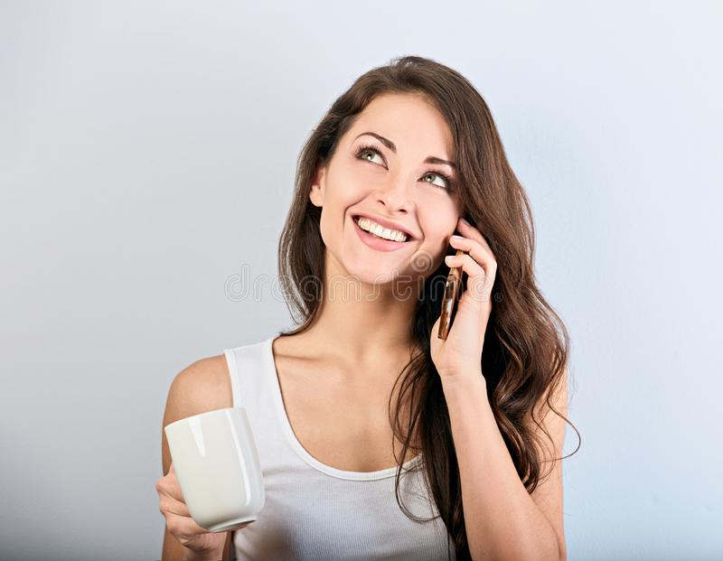 Gelukkige glimlachende mooie vrouw die op mobiele telefoon spreken en kop van koffie op blauwe achtergrond met lege exemplaarruim royalty-vrije stock fotografie