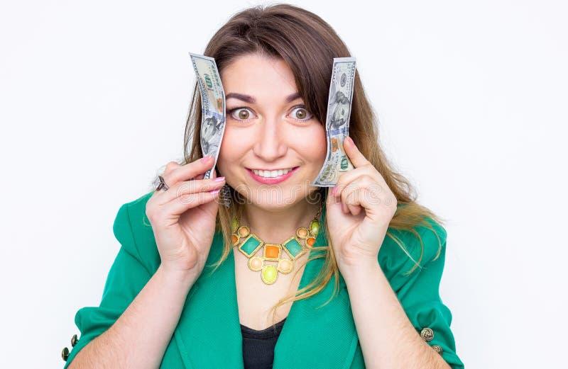 Gelukkige glimlachende onderneemster die in groen jasje met geld dragen Het geld van de vrouwenholding Concept geld stock foto's