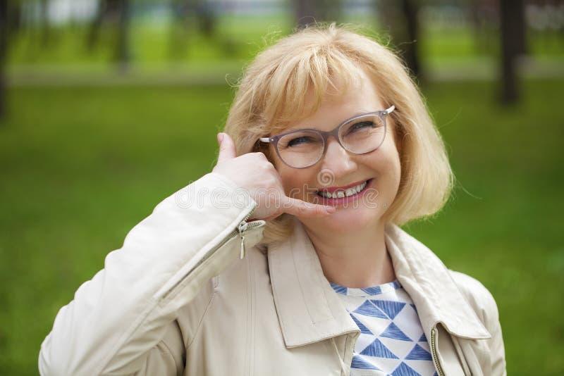 Gelukkige glimlachende oude blondevrouw met vraag me gebaar royalty-vrije stock foto's