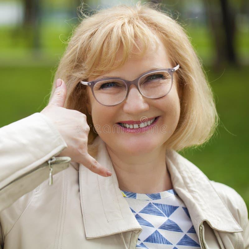 Gelukkige glimlachende oude blondevrouw met vraag me gebaar royalty-vrije stock fotografie