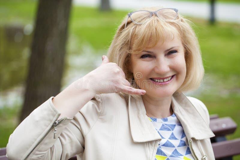 Gelukkige glimlachende oude blondevrouw met vraag me gebaar stock afbeelding