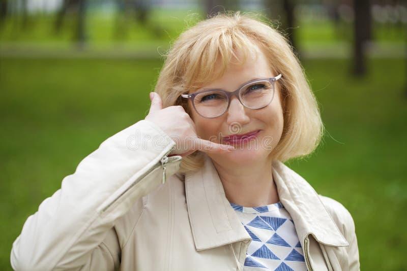 Gelukkige glimlachende oude blondevrouw met vraag me gebaar stock foto's