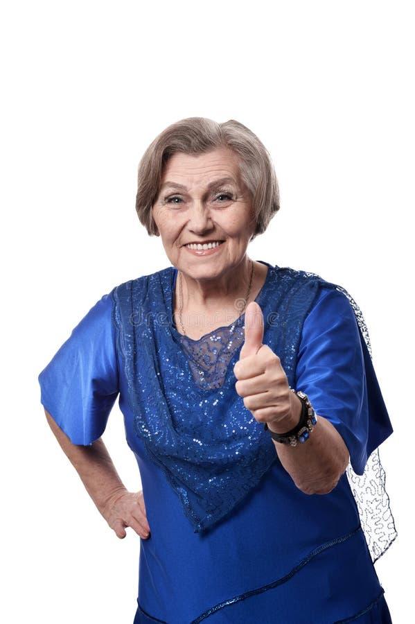 Gelukkige glimlachende oudere vrouw in elegante kleding die duim tonen die omhoog op witte achtergrond wordt geïsoleerd royalty-vrije stock fotografie