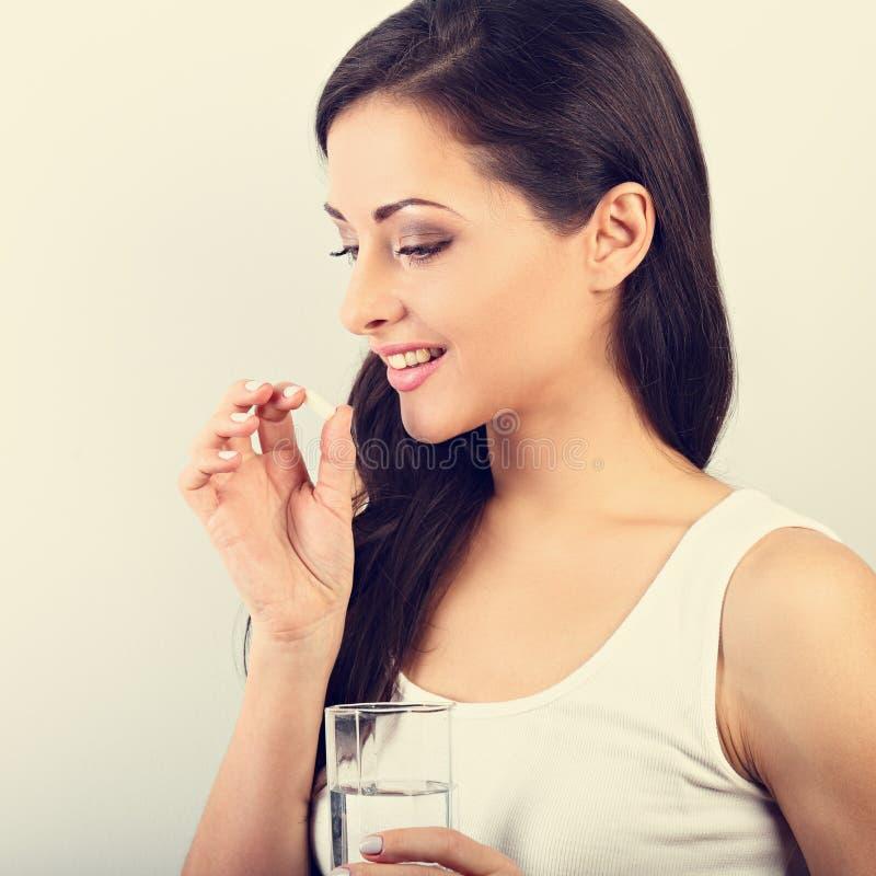 Gelukkige glimlachende positieve vrouw die de pil eten en gla houden royalty-vrije stock fotografie