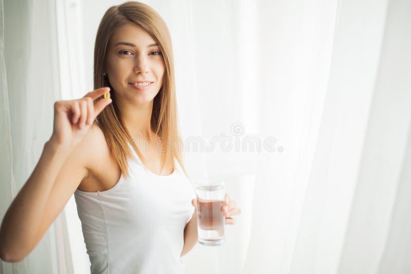 Gelukkige glimlachende positieve vrouw die de pil eten en het glas water in de hand, in haar huis houden royalty-vrije stock fotografie