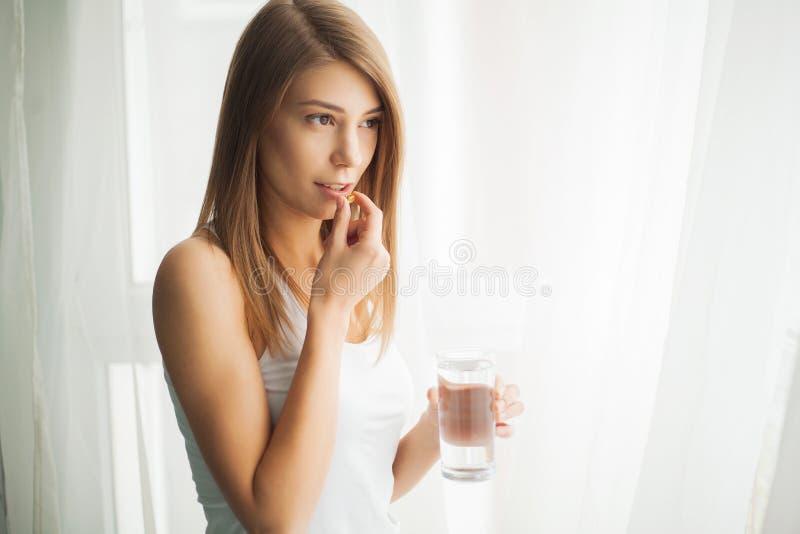 Gelukkige glimlachende positieve vrouw die de pil eten en het glas water in de hand, in haar huis houden stock afbeelding