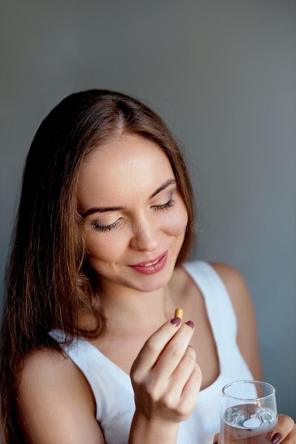 Gelukkige glimlachende positieve vrouw die de pil eten en het glas water in de hand houden, royalty-vrije stock afbeelding