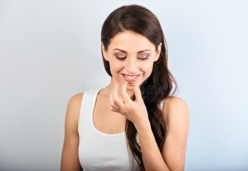 Gelukkige glimlachende positieve vrouw die de pil met vitaminee holding eten in de hand op blauwe achtergrond close-up royalty-vrije stock foto's