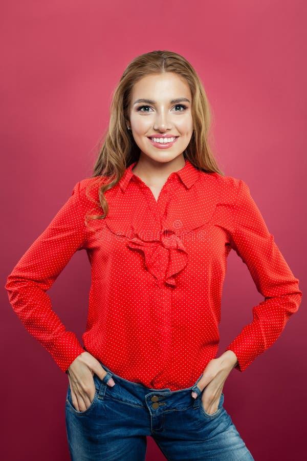 Gelukkige glimlachende positieve vrouw die rode zijdeachtige blouse op heldere kleurrijke roze muurachtergrond dragen Portreit va royalty-vrije stock foto