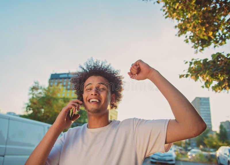 Gelukkige glimlachende stedelijke hipster jonge mens die slimme telefoon met behulp van Afrikaanse Amerikaanse tiener die mobiele stock foto