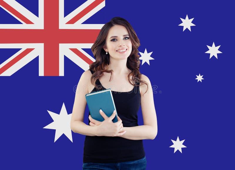 Gelukkige glimlachende studente met boek tegen Australische vlagachtergrond Reis en onderwijs in Australië stock fotografie