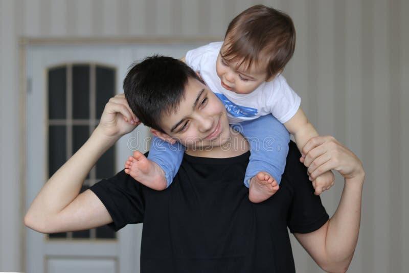 Gelukkige glimlachende tienerjongen die zijn kleine broerzitting op zijn hals houden royalty-vrije stock afbeelding