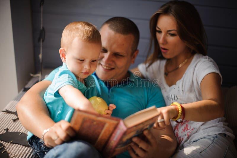 Gelukkige glimlachende vader, moeder en hun klein boek van de zoonslezing stock foto