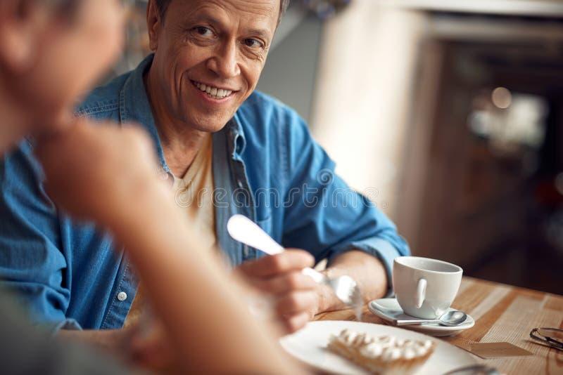 Gelukkige glimlachende verouderde mens die aan wijfje kijken royalty-vrije stock afbeelding