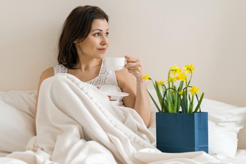 Gelukkige glimlachende volwassen vrouw met boeket van gele bloemen en kop van koffiezitting thuis in bed stock foto