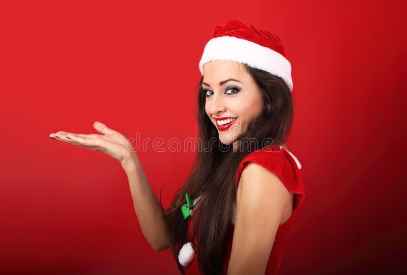 Gelukkige glimlachende vrouw in de kledingsholding en advertis van de Kerstman royalty-vrije stock afbeelding