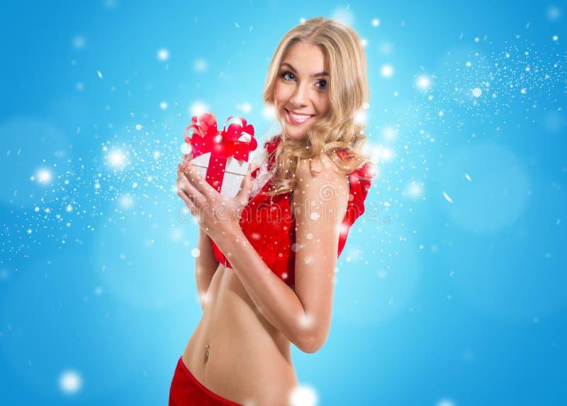 Gelukkige glimlachende vrouw in de kleren van de Kerstman met huidige doos. Bedrieg royalty-vrije stock afbeeldingen